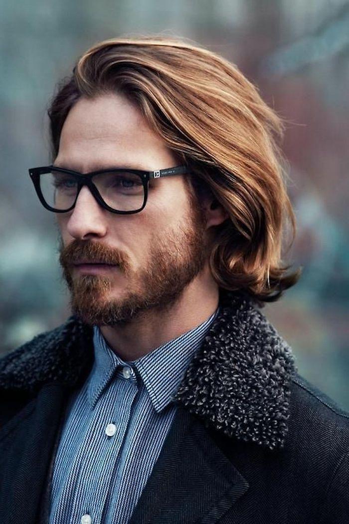 mittellange hellbraune Haarem blaues Hemd mit weißen Knöpfen, Brille mit schwarzem Rahmen
