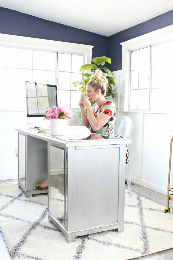 Arbeitszimmer Einrichtung, grauer Schreibtisch, Laptop und Blumenstrauss darauf, grüne Pflanze in der Ecke
