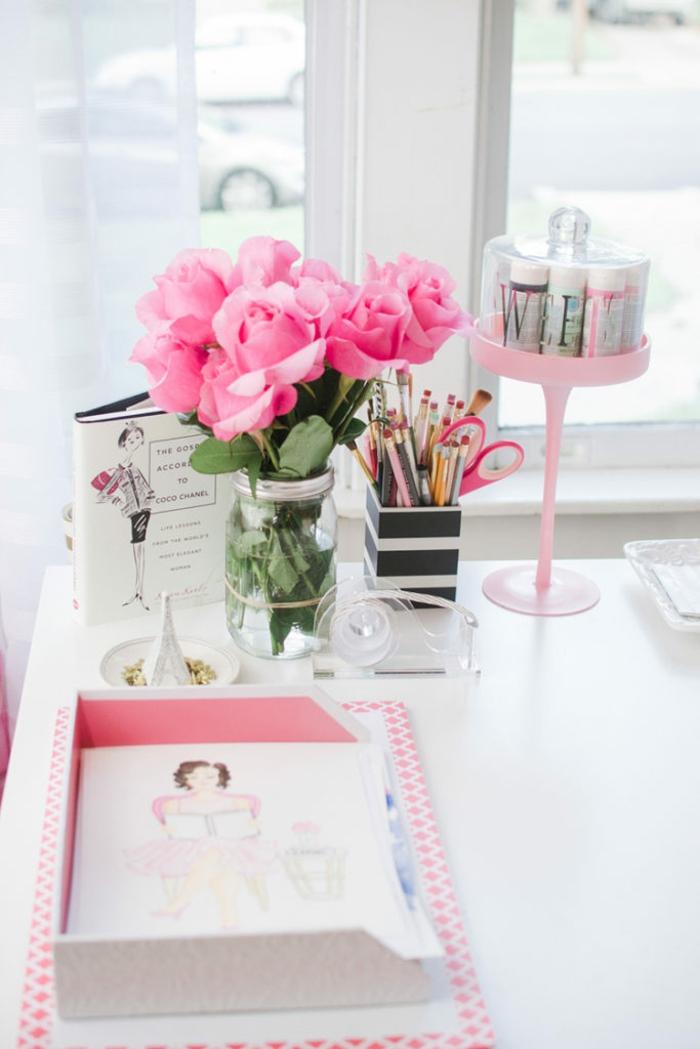 weißer Schreibtisch, Rosenstrauss im Einmachglas, Stifthalter mit vielen Blaustiften und Schere, Bücher und Farben