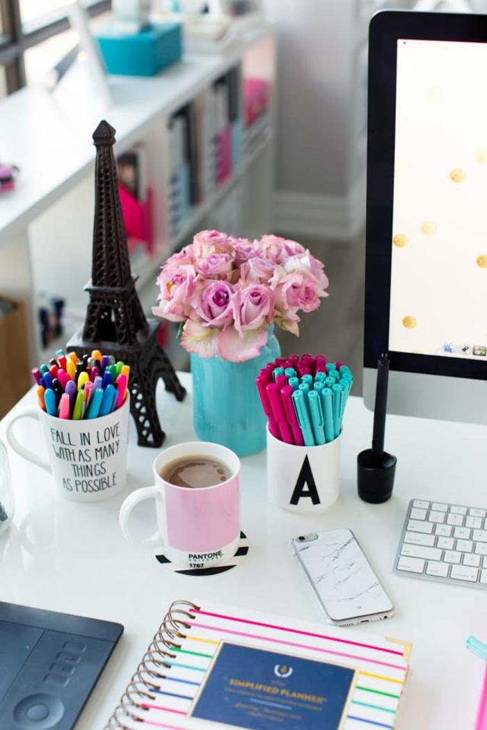 weißer Schreibtisch, Rosenstrauss in blauem Einmachglas, Tassen als Stifthalter, buntes Heft, Tasse Tee, PC und Handy