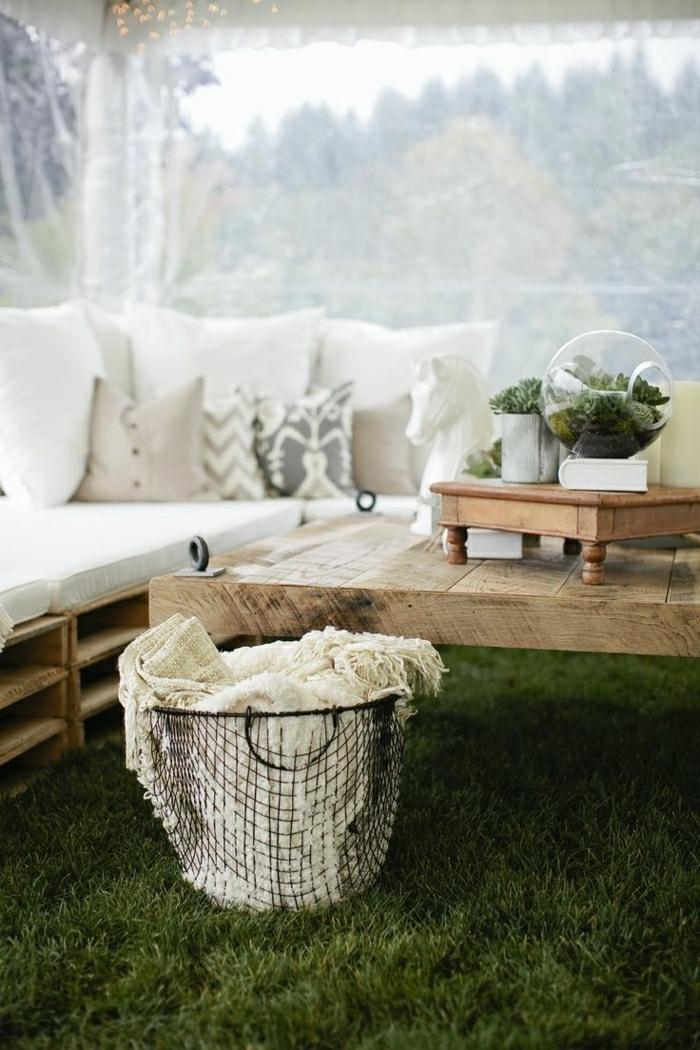 hier finden sie eine sehr schön aussehende palettenmöbel für ihren garten - hier sind sofas aus europaletten und mit weißen kissen und ein kleiner tisch aus holz