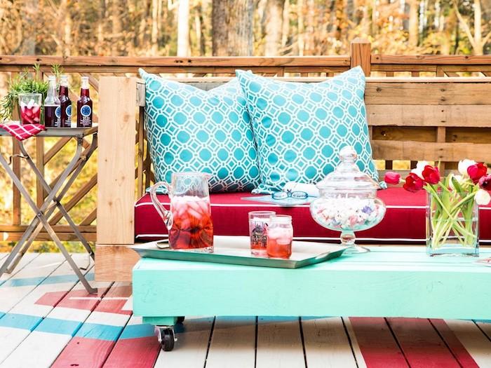 hier zeigen wir ihnen eine ideezum thema gartenmöbel aus paletten - ein kleiner schöner tisch und ein sofa mit blauen kissen, das aus europaletten gebaut ist