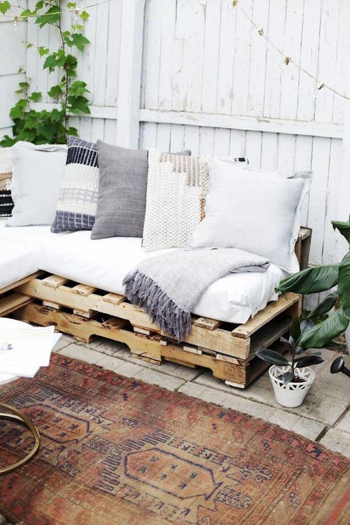einzigartige gartenmöbel aus paletten - hier ist ein sofa aus alten europaletten und mit weißen kissen und ein teppich