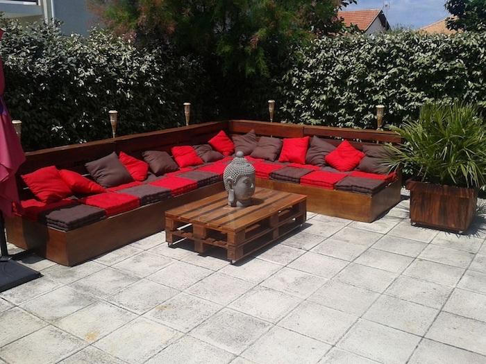 wir empfehlen ihnen einen blick auf dieses bild zu werfen - hier finden sie eine tolle idee für ein sofa mit roten kissen, das aus alten europaletten gebaut ist
