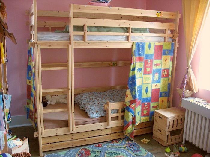 Kinderbett mit bunten Vorhängen interessant bemustert, bunter Teppich und Bettwäsche