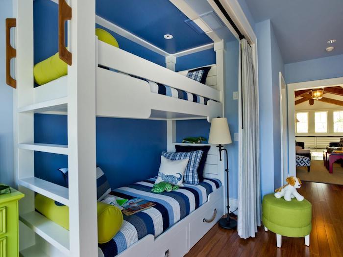 ein blaues Zimmer für zwei Jungen mit einem hohen weißen Kinderbett