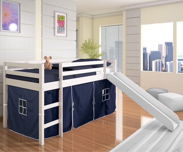 Ein Kinderbett in blauer Farbe mit ein paar kleine Fenster und einem weißen Rahmen