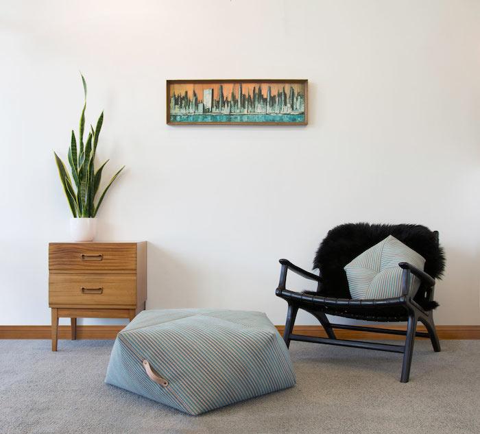 dezentes design im wohnbereich kissen auf dem boden stuhl schwarz minischrank wanddeko blume