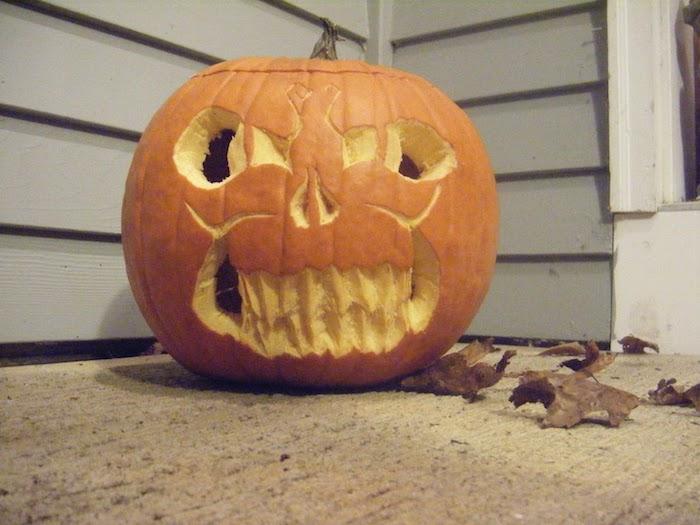 ein gruseliges Gesicht von Kürbis in der Ecke von dem Haus grob geschnitzt