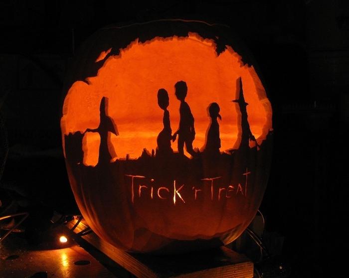 Trick or Treat steht auf diesem Halloween Kürbis mit Silhouetten von maskierten Kindern