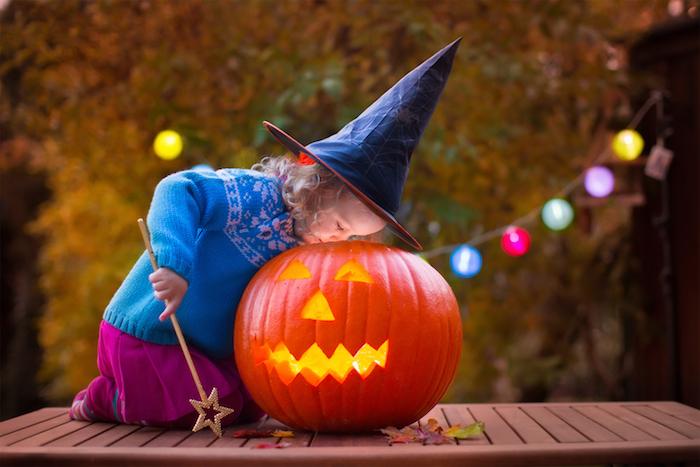 ein kleines Mädchen als Hexe gekleidet spielt mit Kürbisgesicht am Halloween