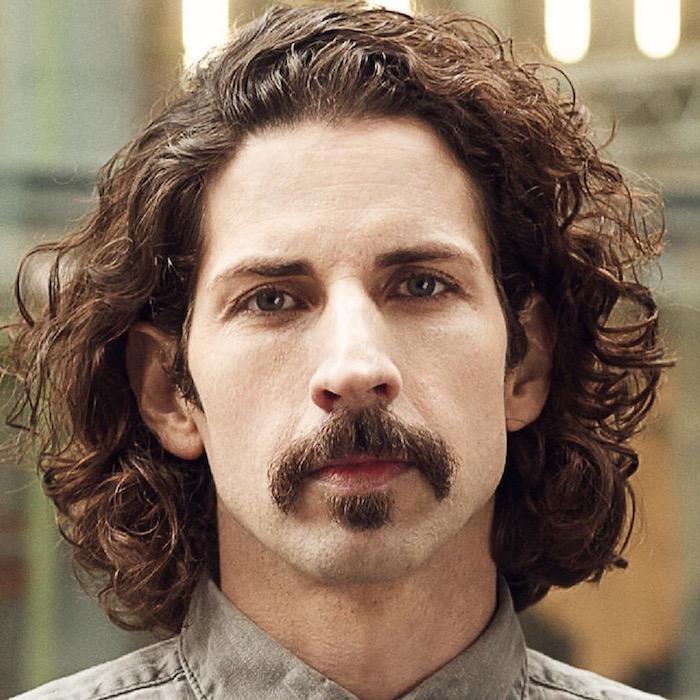 der amerikanische Musiker Frank Zappa mit lockigen mittellangen Haaren und grauem Hemd