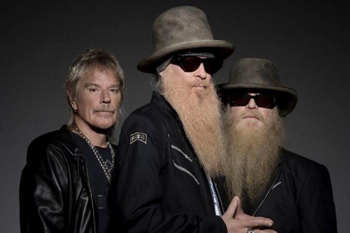 die drei Musiker von ZZ Top mit blonden Haaren, von Kopf zu Fuß in Schwarz