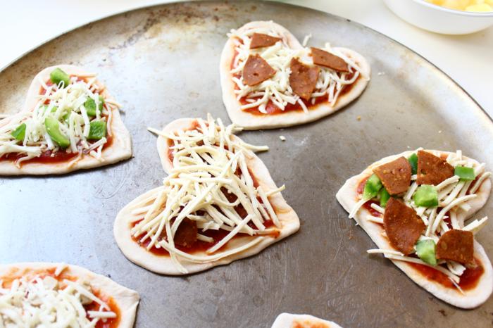 Mini-Pizza zubereiten, Herzen aus Teig schneiden und garnieren, einfache Rezepte für Partys