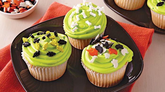 halloween backen, vanille-cupcakes mit grüner creme und kleine figuren aus fondant