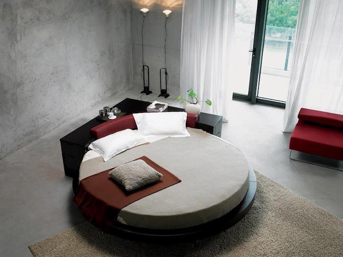 rundes Bett mit rotem Kopfbrett, Bettschrank in Schwarz, zwei Stehlampen neben dem Balkontür