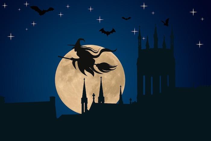 Halloween Hintergrund - eine Hexe am Besen fliegt über einer mittelalterlichen Stadt