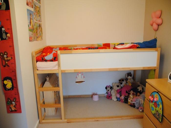 ein Puppenhaus und viele Kuscheltiere unter einem Hochbett für Kinder