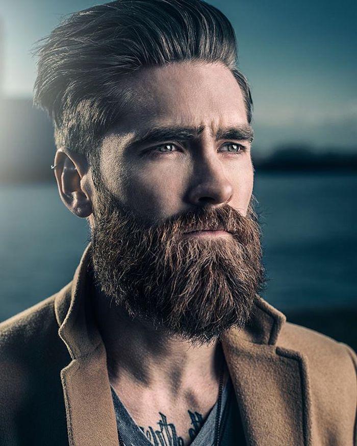 elegant gekleideter Mann mit Vollbart, Helix Piercing, brauner Mantel, Wasser