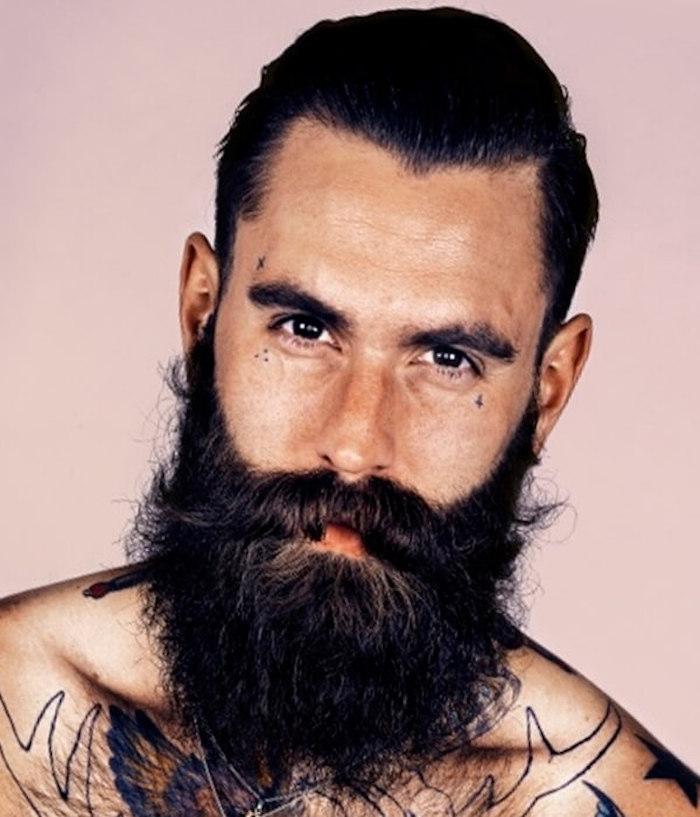 attraktiver Mann mit Brusttattoos, schwarzem langem Bart, Stirntattoo, Wangentattoo