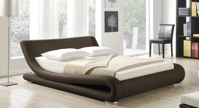 Luxusbetten für zwei Personen mit tapeziertem Bettrahmen, Regal mit vielen Büchern