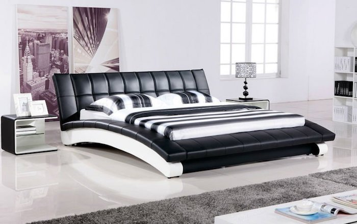 helles Schlafzimmer mit Wasserbett mit Leder-Kopfbrett, weißer Bücherregal in der Ecke
