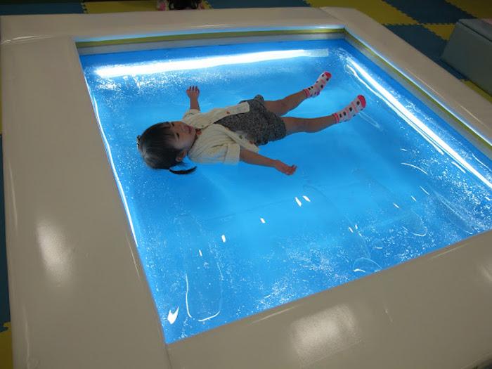 ein kleines Mädchen mit kurzen Haaren liegt auf einer qadratischen Wassermatratze