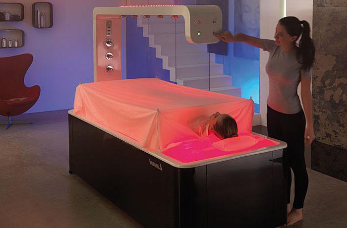 zwei Frauen in einem Wellness Studio, Massagebett mit rotem Licht, Schönheitsprozedur