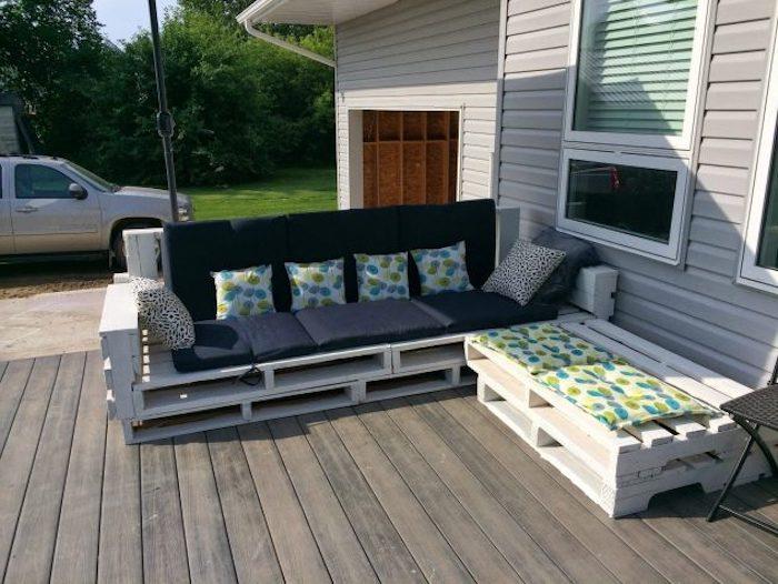 inspirierende idee zum thema palettenmöbel, die ihnen sehr gut gefallen kann - ein weißes sofa mit blauen und weißen kissen und ein kleiner tisch aus weißen europaletten