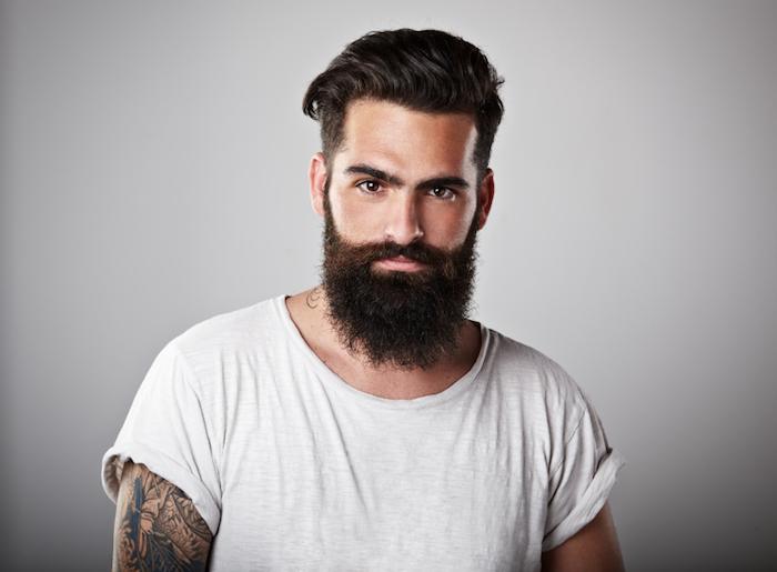 wilder Bartwuchs in Form bringen, Gesicht ohne Falten, Ärmeltattoo, grauer Hintergrund