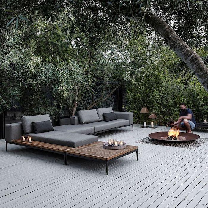 hier zeigen wir ihnen ein bild mit schönen sofas mit grauen und schwarzen kissen in einem garten mit grünen pflanzen