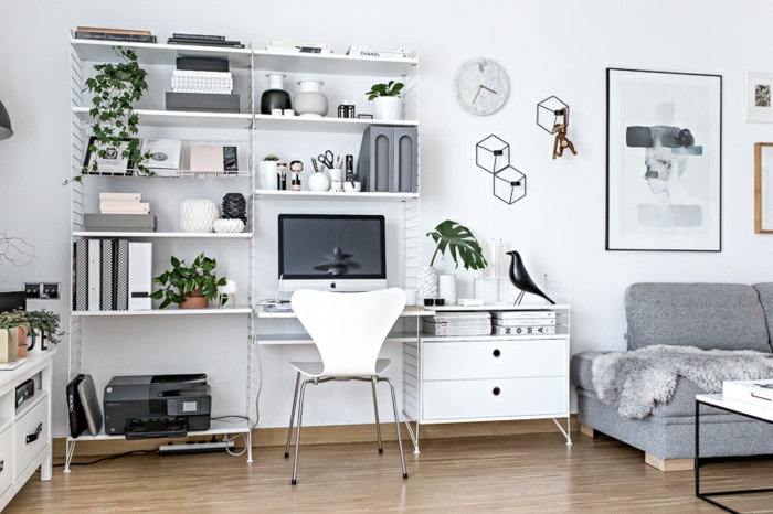 Arbeitszimmer in Weiß, Holzmöbel, grüne Pflanzen, graues Sofa, vielfältige Wanddeko