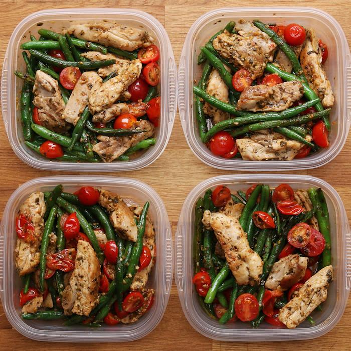 vier Plastikboxen für Mittagessen, Hähnchenfleisch mit gekochten roten Cherrytomaten und grünen Bohnen, lackierter Holztisch