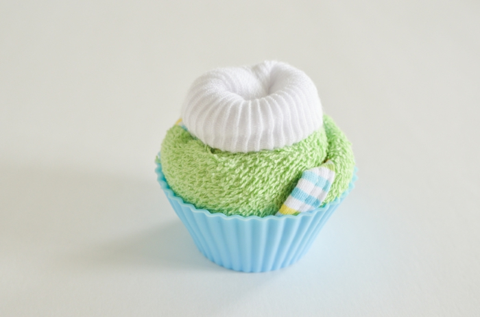 Grünes Tuch und weiße Babysöckchen zum Cupcake rollen, kreatives Babygeschenk, Schritt Sechs