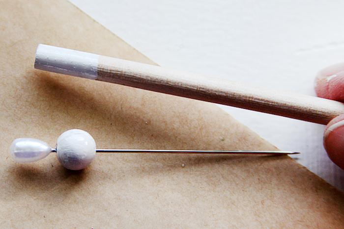weihnachtsgeschenke selbst gemacht, nagel mit weißer perle, kleines holzstäbchen