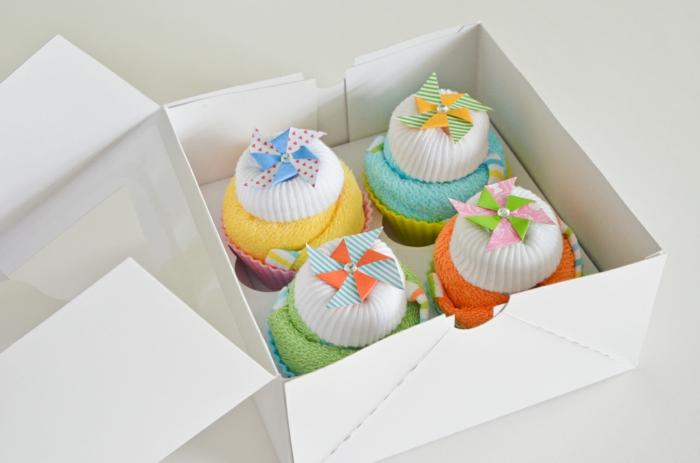 Geschenkideen zur Geburt, vier bunte Cupcakes aus Babysöckchen und Tüchern in weißer Verpackung