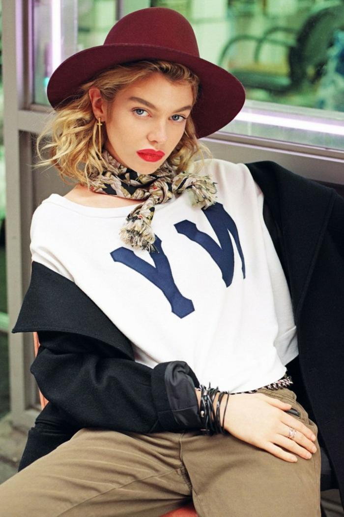 Stella Maxwell in Urban Outfit, weißes Tshirt und weinroter Hut, hellbraune Hose und schwarzer Sakko
