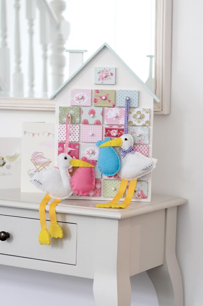 Weißes Häuschen mit vielen bunten Fensterchen, zwei Störche mit Säcken, schöne Dekoration fürs Babyzimmer