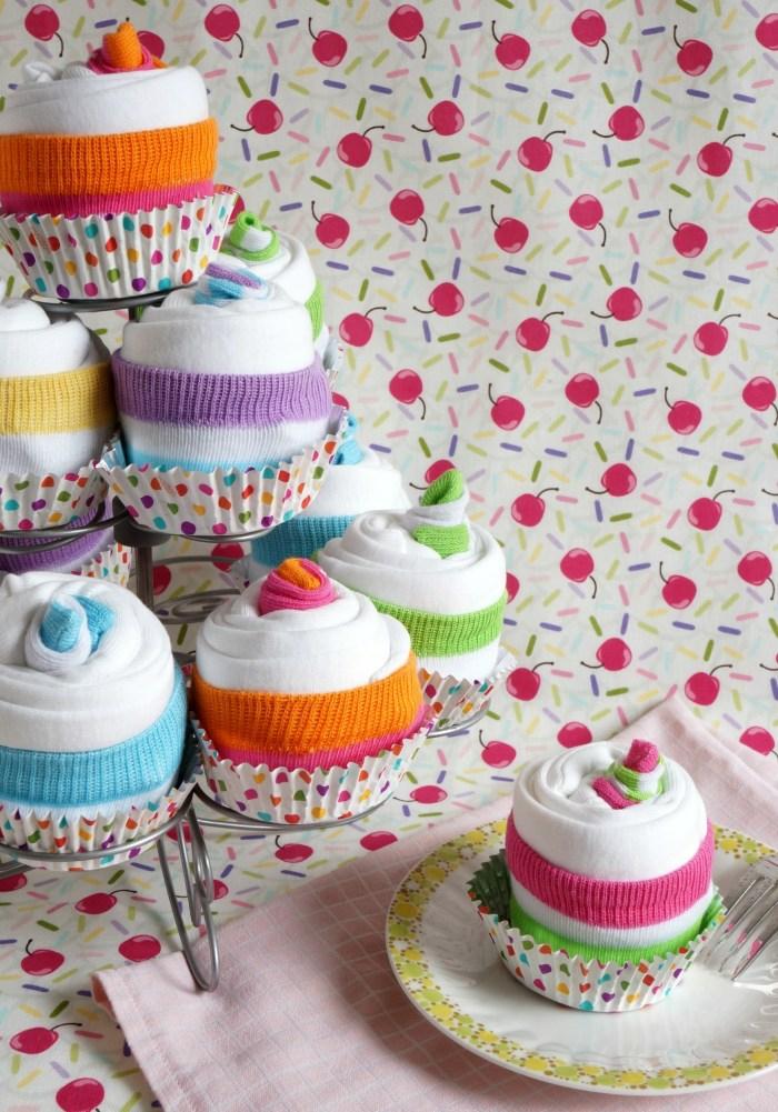 kreative Idee für Babygeschenk, bunte Cupcakes aus Babysöckchen und Tüchern in Muffinförmchen