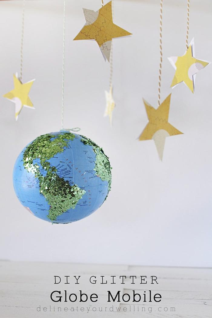 Selbstgemachte Mobile, gelbe Sterne aus Papier und Globus verziert mit Glitter, schönes Babygeschenk