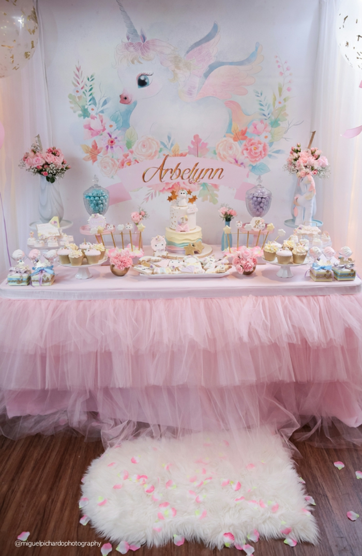 Babyparty für Mädchen, süßes Einhorn an der Wand, Tisch mit rosa Decke, viele Cupcakes und Tarten, zwei große Blumensträusse