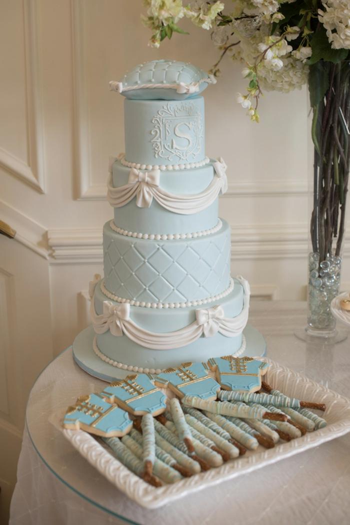 Babyparty für einen Jungen, blaue vierstöckige Torte, kleine Kekse für die Gäste, großer Blumenstrauß in Glasvase