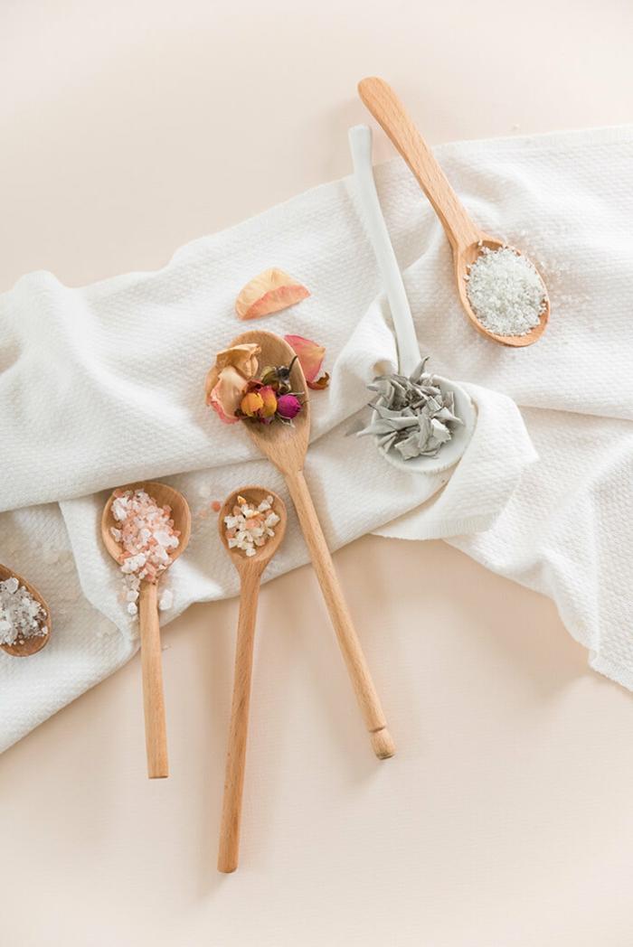 Badesalz mit Rosenblüten selber machen, in Kochlöffeln, auf weißem Tuch platziert