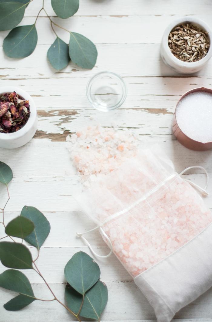 hausgemachtes Badesalz in weißem Säckchen, Rosenblätter daneben, Blüten und Kräuter für Entspannung