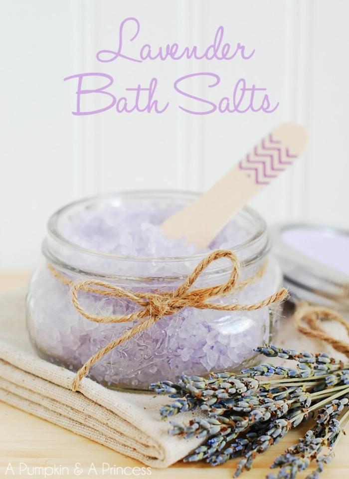 Badesalz mit Lavendeln, kleines Einmachglas, mit Faden verziert, Lavendelblüten daneben