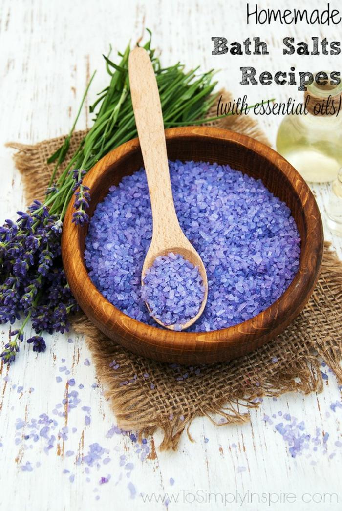 Hausgemachtes Badesalz mit Lavendel in Holzschale, Kochlöffel darin, Lavendelblütel daneben