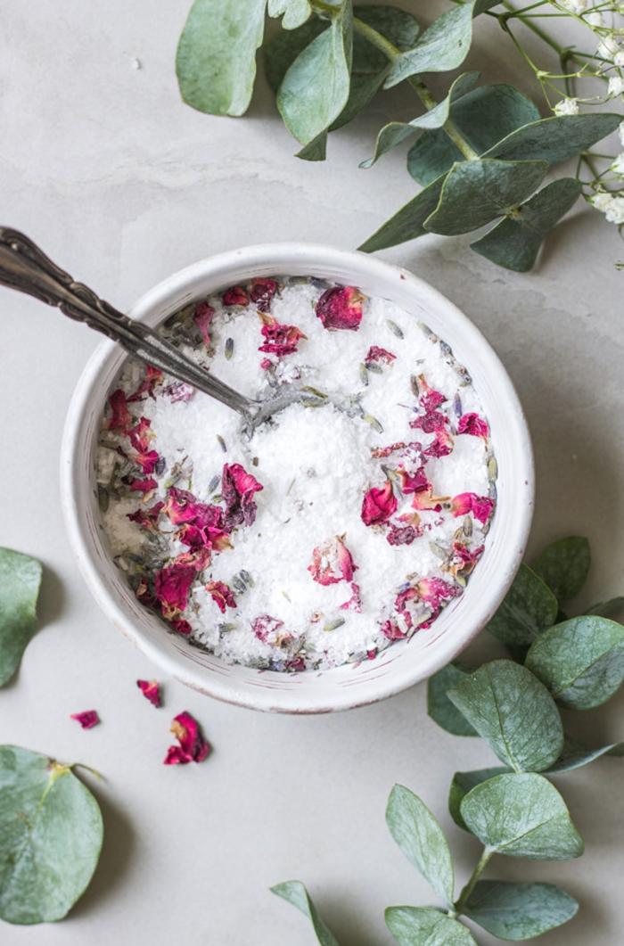 hausgemachtes Badesalz mit Rosenblüten in Porzellan Schale, Rosenblätter daneben, schnelles und einfaches Rezept