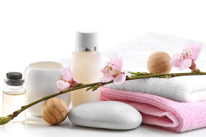 bio kosmetik, zweig mit blüten, duschgel aus naturprodukten, heutpflege