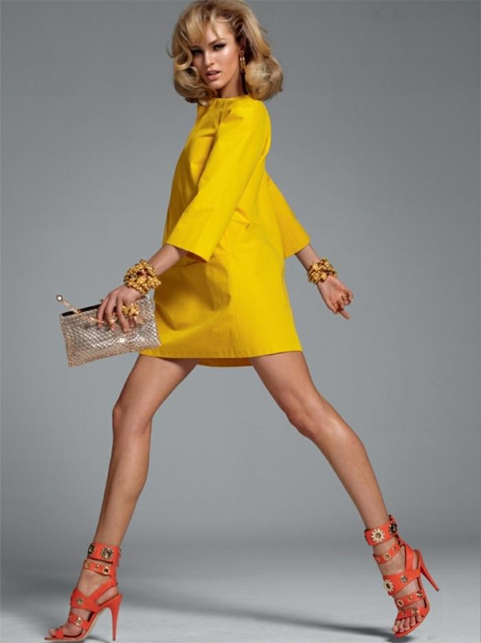 Blonde Haare, tolle mittellange Frisur, olivenfarbener Teint, gelbes Kleid mit langen Ärmeln, orange High Heels, silberne Handtasche, auffällige Armbänder