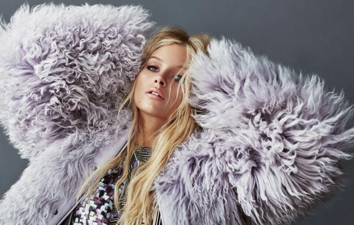 lange blonde Haare, matter Lippenstift und schwarze Mascara, lila Pelzmantel, Top mit Pailletten